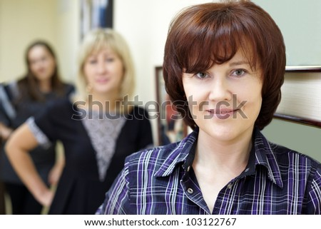 Three women stand near the wall, focus on the face of the first of them in checkered shirt - stock photo