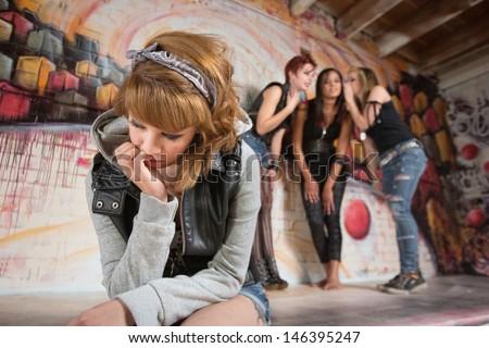 Three women talking about sad teenager sitting alone - stock photo