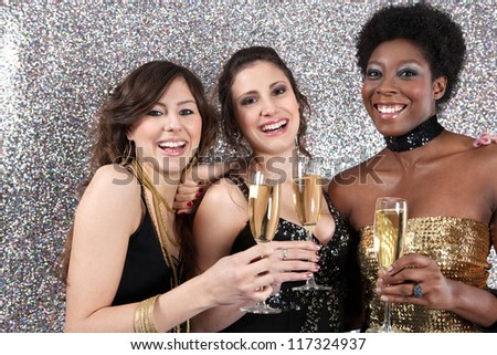 Three women toasting with champagne at a party against a silver glitter background. - stock photo