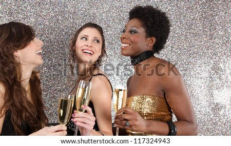 Three women toasting with champagne at a party against a silver glitter background, laughing. - stock photo