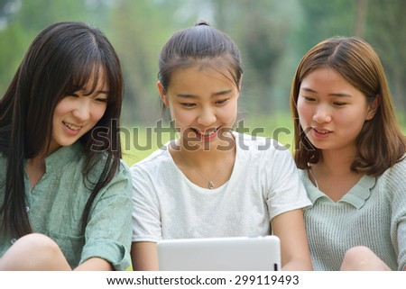 Three women together watching a tablet.Asian people - stock photo