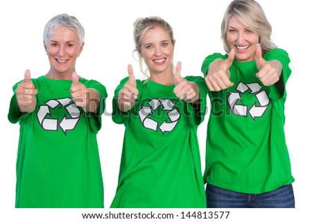 Three women wearing green recycling tshirts giving thumbs up on white background - stock photo
