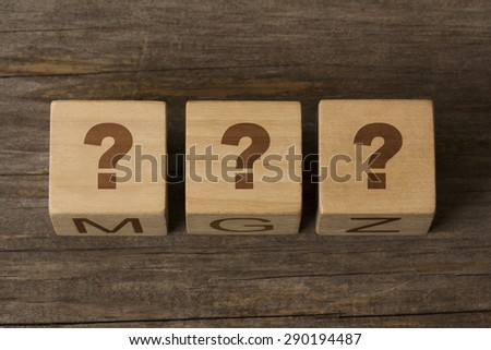 three wooden cubes displaying question marks on a wooden background - stock photo