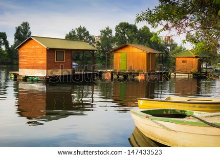 three wooden houses on the barrel floating on the river with two boats in the foreground.  - stock photo