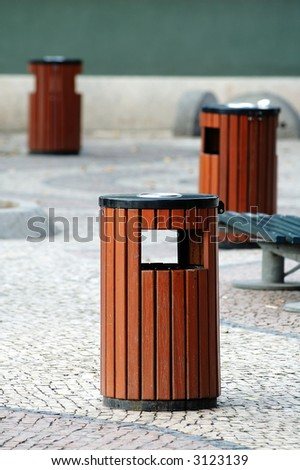 Three wooden litter bins in public area - stock photo