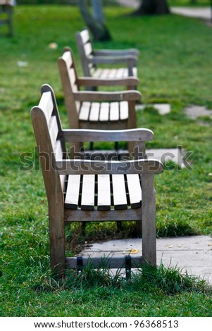 three wooden Park Bench's in a row at a sunny park - stock photo