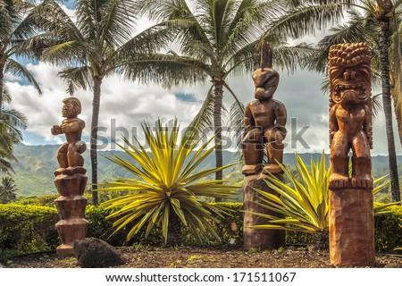 Three wooden Polynesian tiki carvings on Oahu, Hawaii - stock photo