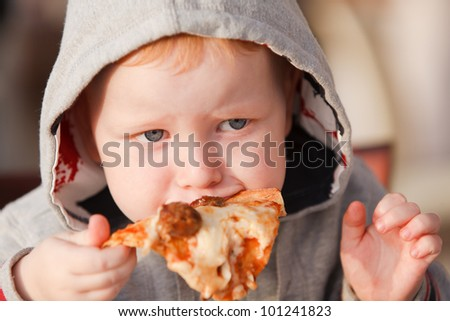 Three year old boy eating a slice of pizza. - stock photo