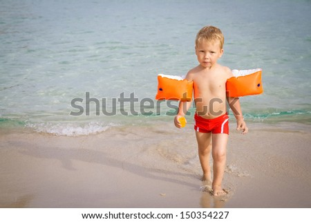 Three year old boy playing on the beach  - stock photo