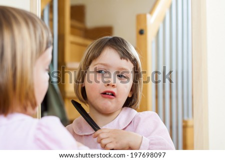 three year old child   brushing her hair - stock photo