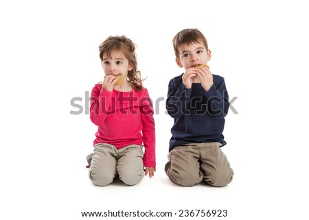 Three year old fraternal boy and girl twins eating cookies isolated on white background - stock photo