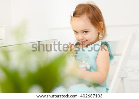 three year old girl with brown hair and large blue eyes in a pink fluffy skirt and sneakers. with beautiful spring flowers and smiling. white Studio - stock photo