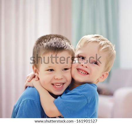 Three-year-old twins embrace - stock photo