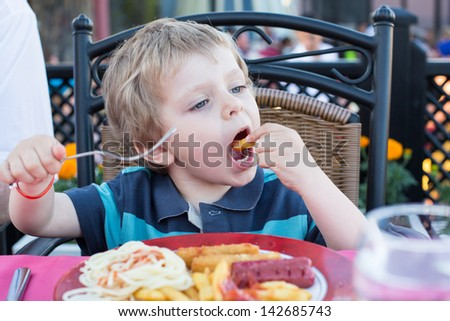 Three years old boy eating french fries in summer, outdoors - stock photo