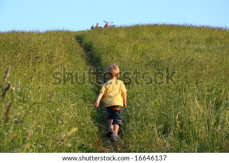Three years old boy running on the top of the hill - stock photo