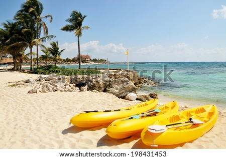 Three yellow kayaks and paddles sit on the tropical white sandy beach town of Riviera Maya, Mexico  - stock photo