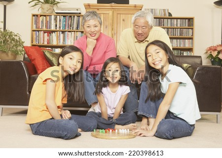 Three young Asian sisters playing chinese checkers while grandparents watch - stock photo