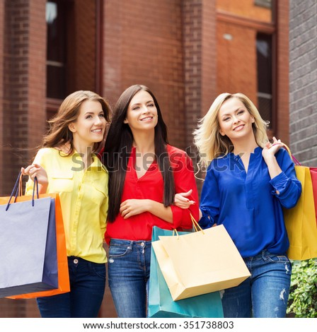 Three young beautiful female friends walking with shopping bags in city center. - stock photo