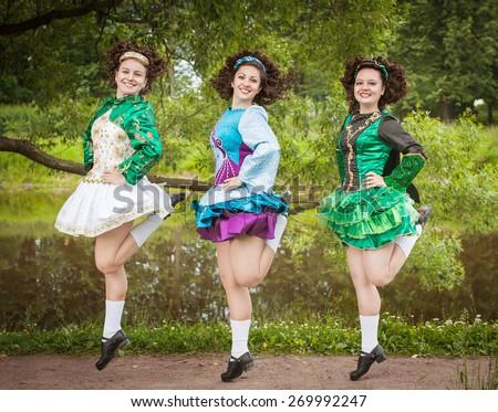 Three young beautiful girls in irish dance dress and wig dancing outdoor - stock photo