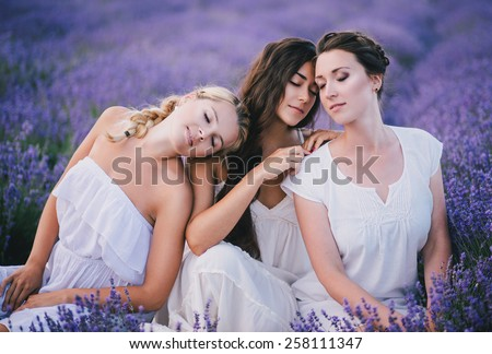 Three young beautiful women in white dresses posing together in a lavender field - stock photo