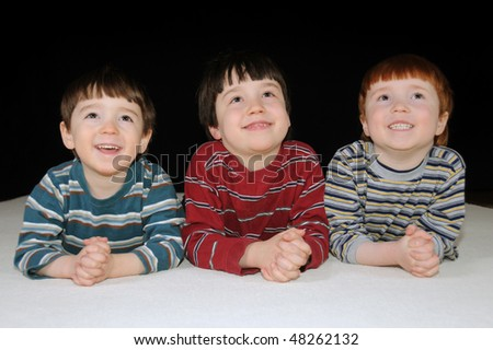 Three young boys watching a movie on television - stock photo
