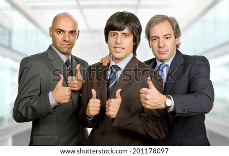 three young business men going thumbs up, at the office - stock photo