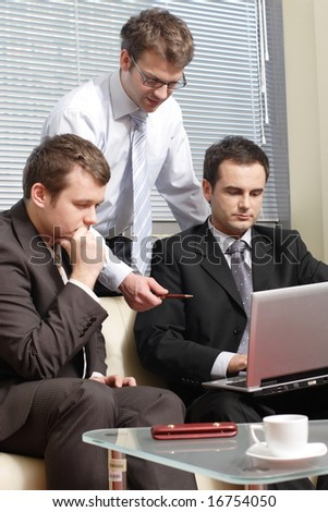 Three young business men working  together with laptop in the office - stock photo