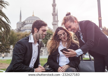 Three young business team Working in front of Blue Mosque in Istanbul - stock photo