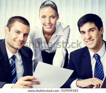 Three young businesspeople working with document at office, teamwork concept   - stock photo