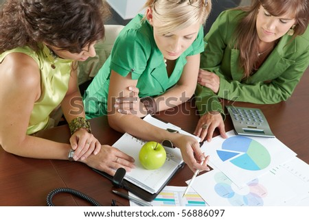 Three young businesswomen sitting at meeting room, discussing financial charts on table. Overhead shot. - stock photo