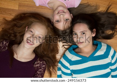 Three young, diverse  girls  lying on a wood floor looking up at the camera. One African American with red hair, one hispanic and one caucasian - stock photo