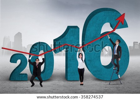 Three young employers lifting upward arrow with numbers 2016, shot outdoors - stock photo