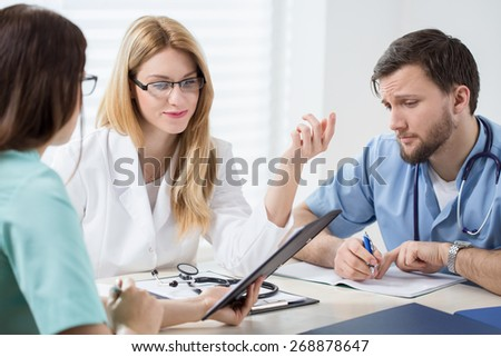 Three young experienced doctors planning pateint's treatment - stock photo