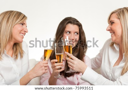 Three young female friends toasting with flutes - stock photo
