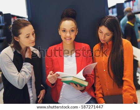 Three young female students standing in public library with books. Young women sharing books for theirs studies. - stock photo