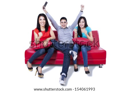Three young friends cheering at television isolated on white - stock photo