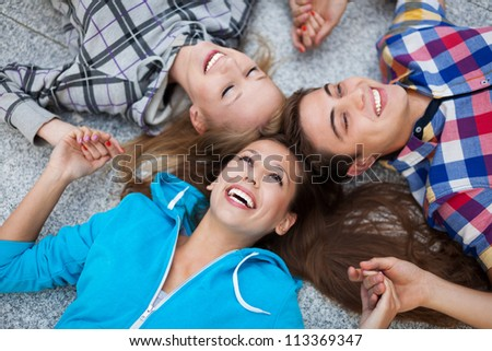 Three young friends lying down - stock photo