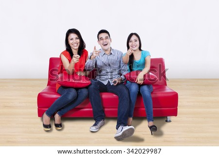 Three young friends pointing their fingers at home - stock photo