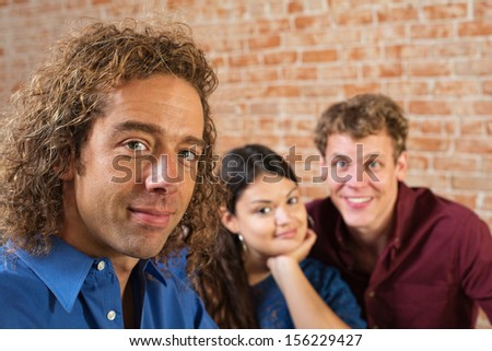 Three young friends sitting together indoors - stock photo