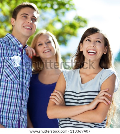 Three young friends standing together - stock photo