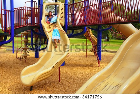 Three young girls climbing on slide at playground - stock photo