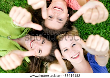 Three young girls lying down showing thumbs up sign - stock photo