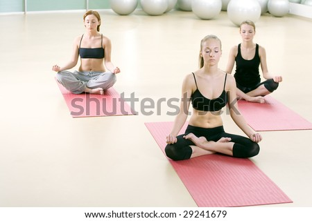 Three young girls meditate in sports gym - stock photo