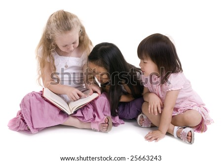 Three young girls sharing a book. Diversity in friends - stock photo