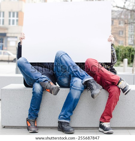 Three young happy boys holding a blank white card - stock photo
