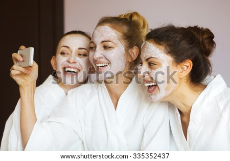 Three young happy women with face masks taking selfi at spa resort. Frenship and wellbeing concept - stock photo