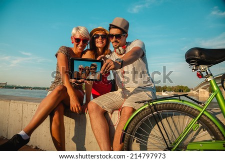 Three Young Hipster Friends Near River Taking Selfie Using Digital Tablet - stock photo