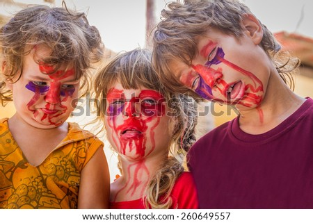 three young kids - boy and girl - with painted faces, child zombie face art - stock photo