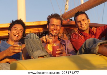 Three young laughing men sitting on a boat - stock photo