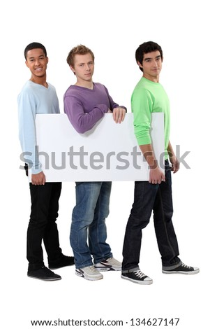 Three young men carrying a blank board - stock photo